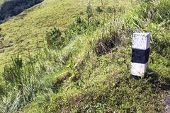Black and white concrete pillar in lush green hill Stock Photos