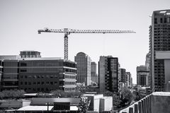Black and white of Construction Crane in Downtown Austin Texas building a larger skyline in the Capital City. Side view of the long crane stock photo