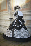 Black and white costumed masked woman. At San Zaccaria in Venice Royalty Free Stock Photos