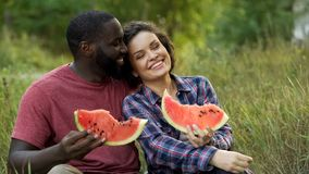 Black and white couple enjoying themselves and eating delicious watermelon stock photos