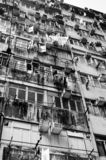 Black and white cramped residential apartment building in the Asian city. Old rusty residential public housing apartment building with clothing hanging on royalty free stock image