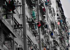 Black and white cramped residential apartment building in the Asian city. Old rusty residential public housing apartment building with clothing hanging on royalty free stock photos