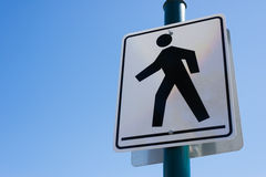 Black and white crosswalk sign over a clear, blue sky background Stock Image