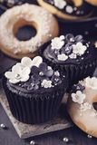 Black white cupcakes and donuts. On a dark wooden background Royalty Free Stock Photo