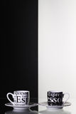 Black and white cups  of coffee on a glass table Stock Images
