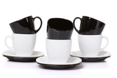 Black on white cups with stack plates. Black on white cups with stack plates on white background royalty free stock photography