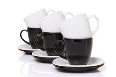 Black and white cups on the stack of the plates. Stock Photography