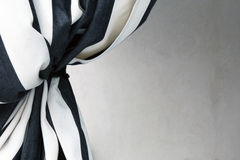 Black and white curtain tied back to present white background Royalty Free Stock Photography
