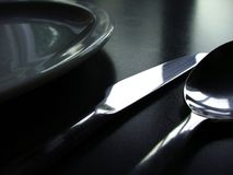 Black and white cutlery. Close up of a plate and cutlery, set on a black table top Stock Photography
