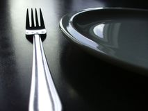 Black and white cutlery. Close up of a plate and cutlery, set on a black table top Royalty Free Stock Photo