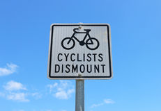 Black and white Cyclists Dismount sign in a blue sky Stock Images