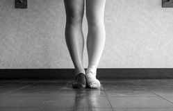 Black and white Dancer standing in parallel position at the barre, half dress in Jazz dance attire and half in ballet attire Stock Photography