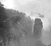 Black and white dashed retro sketch. Autumn early morning, fall valley. Sandstone peaks and hills increased from heavy mist. Royalty Free Stock Photo