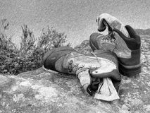 Black and white dashed retro sketch. Hiker high boots and sweaty grey socks. Resting on the boulder at  stream Royalty Free Stock Images