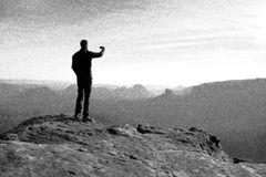 Black and white dashed retro sketch. Hiker is taking photo by smart phone on the peak of rock Royalty Free Stock Photos