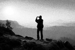 Black and white dashed retro sketch. Hiker is taking photo by smart phone on the peak of rock Stock Photography