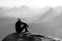 Black and white dashed retro sketch. Moment of loneliness. Man sit on the peak of rock and watching into mist and fog in valley. Stock Image