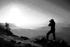 Black and white dashed retro sketch. Professional photographer takes photos with mirror camera on peak of rock. Dreamy fogy landscape Royalty Free Stock Photography