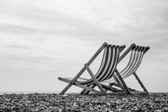 Black and White Deck Chairs on Brighton Beach, England Stock Image