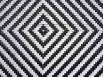 A black and white diamond pattern formed in woven plastic as a background royalty free illustration