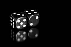 Black and White Dice Reflected on Black. A pair of black and white dice, reflected on a black surface royalty free stock images
