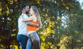 Black and white diversity couple dancing in the park stock photo