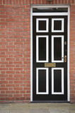 Black and white door with a brick wall Stock Photo