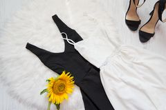 Black and white dress, shoes and sunflower on white fur. Fashionable concept, top view Stock Photography