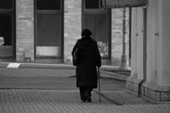 Black and white elderly woman with a stick walking down the street. Black and white elderly woman with a stick walking along a city street past houses stock image