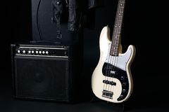 Black and white electric bass guitar with amplifier, hard case Royalty Free Stock Images