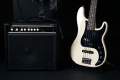Black and white electric bass guitar with amplifier, jack cable,. Hard case and Leather biker jacket Royalty Free Stock Photography