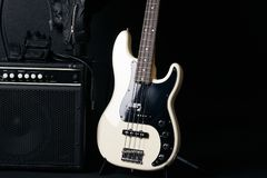 Black and white electric bass guitar with amplifier,jack cable,hard case and Leather biker jacket Stock Photo