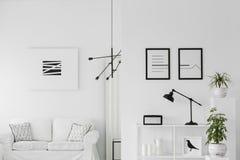 Black and white elegant interior. Black lamp on white shelf in elegant living room interior with minimal poster above settee stock photography