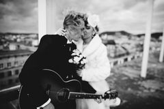 Black and white emotional portrait of happy bride and groom with guitar having fun and jumping on the roof. Blurred stock image