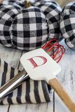 Black and White Fall Deco. Black and white pumpkins on rustic whitewashed boards with red whisk and red monogrammed `D` spatula. Contemporary fall royalty free stock photos