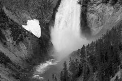 Black and White Falls. This was the base of a large waterfall at Yellowstone National Park. There were dark trees to the right and a white snow patch to the left Stock Photo