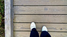 Black &White feet on wood. The path. A weathered wooden plank footbridge is the background for walking the path. White shoes and black cuffs invite you to join Stock Photography