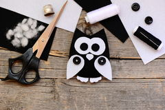 Black and white felt owl, felt sheets, scissors, threads, thimble, buttons on a vintage wooden table. Creating pretty owl ornament. Felt crafts. Wool felt crafts Stock Image