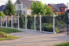 Black-white fence with a wicket in front of a private garden and a house on the street Royalty Free Stock Photo