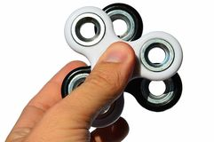 Black and white fidget spinners stacked together and held between thumb and index finger of adult male person, white background. Natural sunlight royalty free stock images
