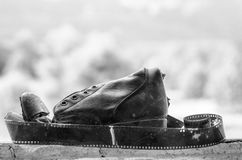 Black and white Film and old ripped boot on window black. Ripped military boot on window and film Royalty Free Stock Image