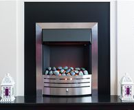 Chrome fire surround with light from the coals. Black and white fire surround with ornamental lanterns at the sides, flower vases on the top of the fire place Royalty Free Stock Image