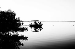 Black and white of fishing boat on calm water in early morning w stock photos