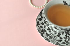 Black and white floral porcelain tea cup with tea on pastel background top view with copy space Stock Images
