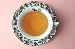 Black and white floral porcelain tea cup with tea on pastel background top view with copy space. Black and white floral porcelain tea cup with tea on pink peach Royalty Free Stock Image
