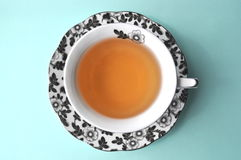 Black and white floral porcelain tea cup with tea on pastel background top view with copy space Royalty Free Stock Photography
