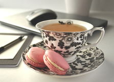 A black and white floral tea cup with pink French macaroons on a table with laptop computer and a mouse - a  work from home workst. A black and white floral tea Royalty Free Stock Photo