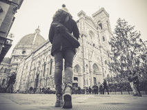Black and white florence italy woman walking towards the cathedral with backpack at Christmas. Florence italy woman walking towards the cathedral with backpack stock image
