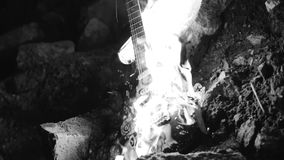 Black and white footage of a burning electric guitar. The atmosphere of the Apocalypse.