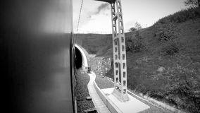 Black and white footage: fast going train enters the tunnel and exits it.  stock video
